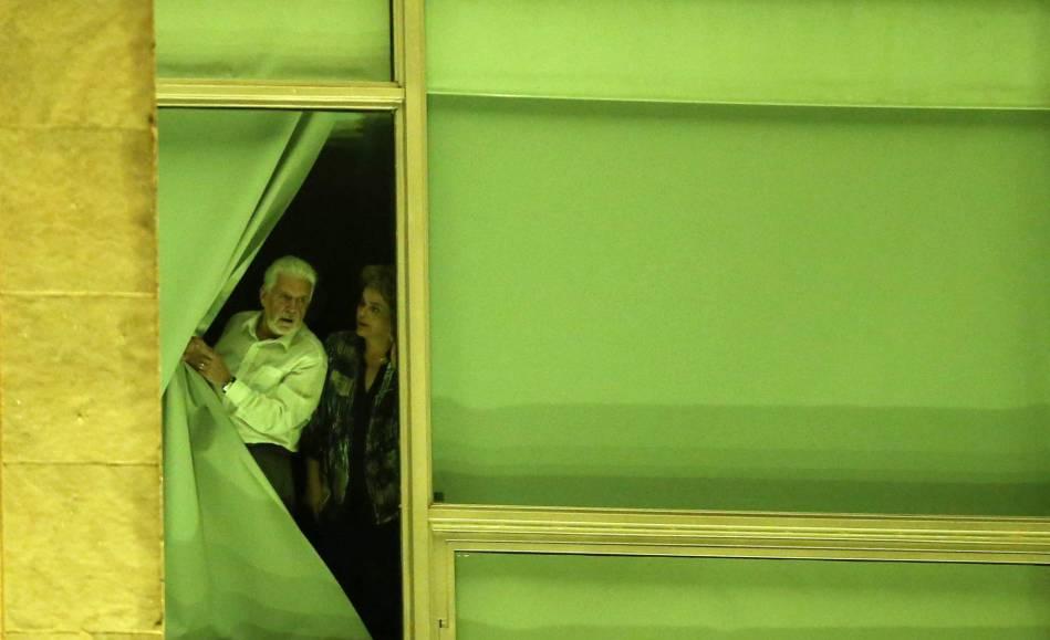 Dilma e o ministro Jaques Wagner espiam pela janela a movimentação do lado de fora do Palácio do Planalto. ADRIANO MACHADO REUTERS