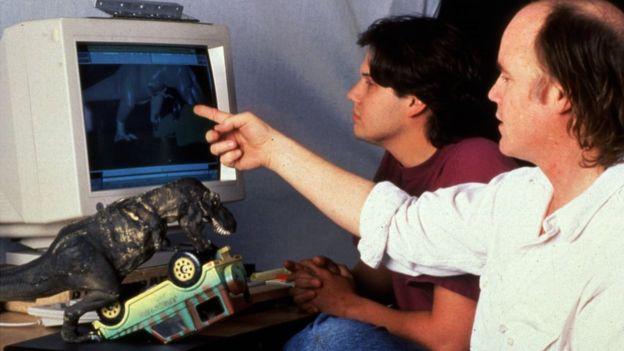 Dois homens olham para uma tela de computador do final dos anos 1990 com uma animação de dinossauro visível. Um boneco de dinossauro e um jipe estão na mesa ao lado deles.