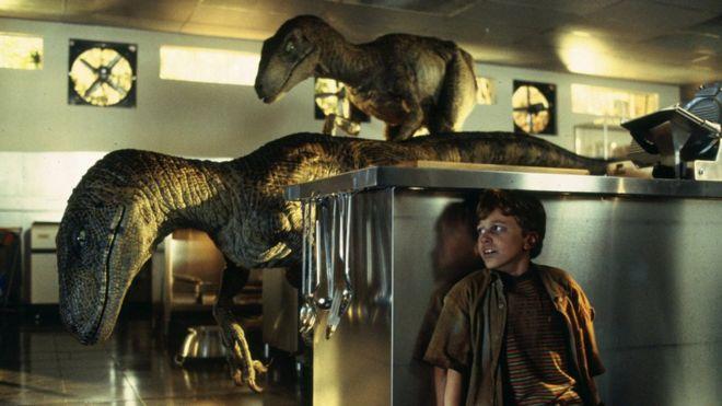 Cena do filme Jurassic Park – o personagem Tim se esconde de dois velociraptors na cozinha