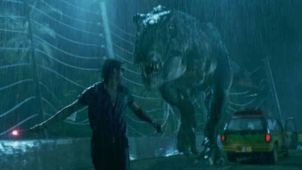 Homem foge de um T. rex na chuva
