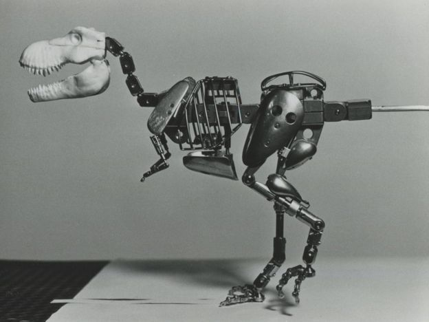 Uma imagem em preto e branco de um modelo de tiranossauro de metal