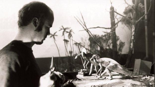 Foto em preto e branco de um homem trabalhando com bonecos de dinossauros