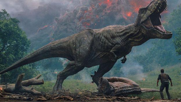 Cena do filme Jurassic Park: Reino Ameaçado, em que um enorme dinossauro ruge obervado pelo personagem principal, com cenas de um vulcão em erupção no fundo