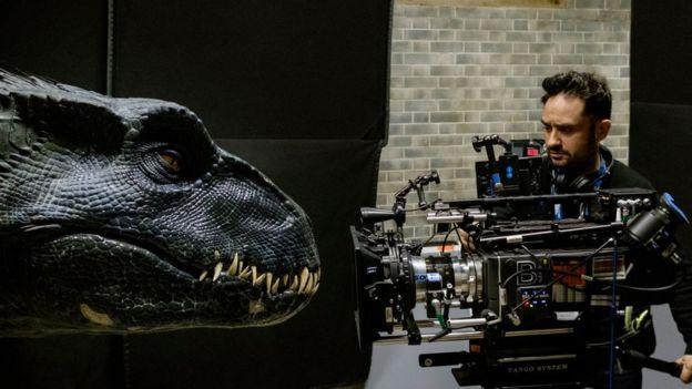 Um cinegrafista segura uma camera apontada para um robô de dinossauro durante a filmagem do longa 'Jurassic World: Reino Ameaçado'