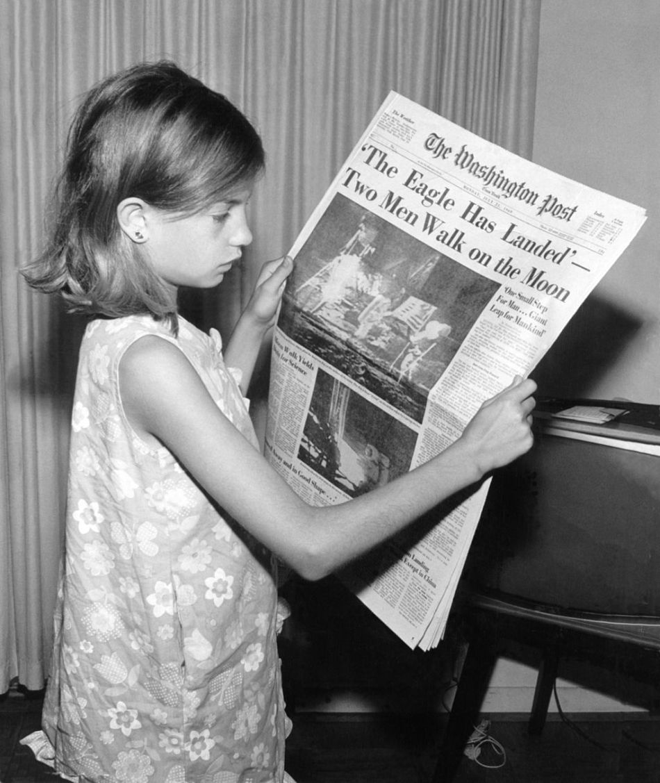 Uma menina segura o jornal Washington Post do dia 21 de julho de 1969 com a manchete - A Águia Pousou - Dois Homens Caminham na Lua.