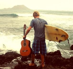 18 de Maio - 1975 — Jack Johnson, cantor estadunidense, com violão e prancha de surfe.