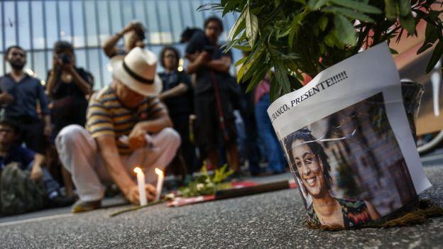 Foto de Marielle Franco ao lado de pessoas que acendem velas e prestam homenagem à vereadora