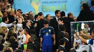 24 de Junho - Messi pega o troféu de melhor jogador da Copa de cabeça baixa, após perder da Alemanha na final.