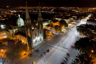 14 de Abril - Botucatu, São Paulo - tomada aérea - igreja e avenida à noite, iluminada.