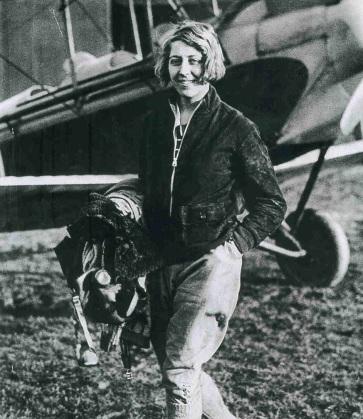 1 de Julho - Amy Johnson, aviadora norte-americana, junto ao avião, sorrindo.