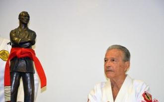 1 de Outubro - Hélio Gracie - 1913 – 104 Anos em 2017 - Acontecimentos do Dia - Foto 16 - Robson Gracie observa a estátua de Hélio Gracie ornada com a faixa-vermelha do mestre.