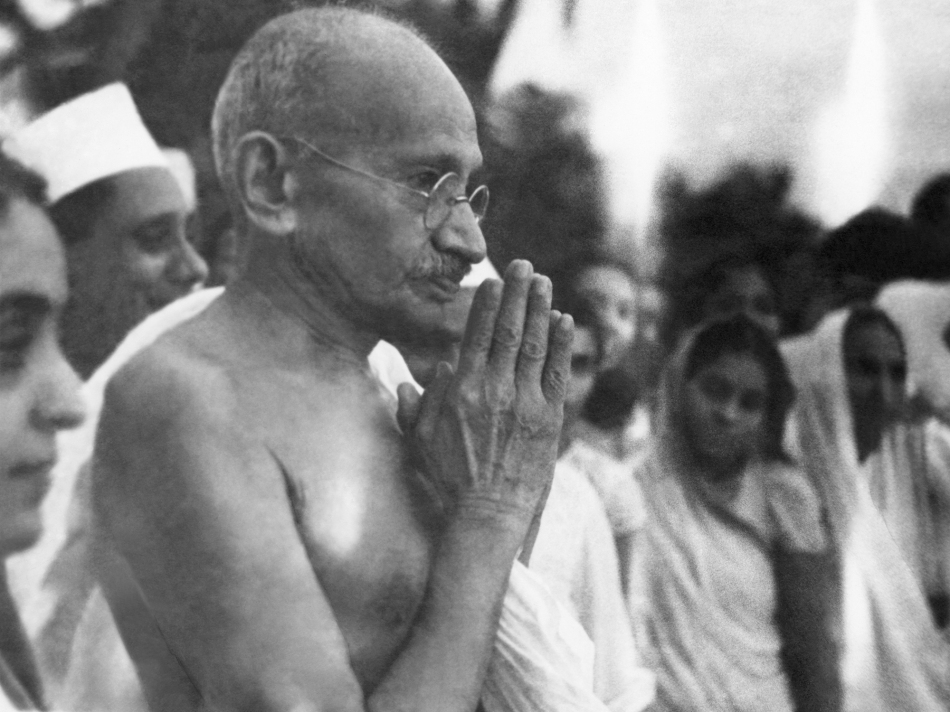 Indian statesman and activist Mohandas Karamchand Gandhi (1869 - 1948) greeting people at Juhu Beach, Mumbai, May 1944. (Photo by Dinodia Photos/Getty Images)
